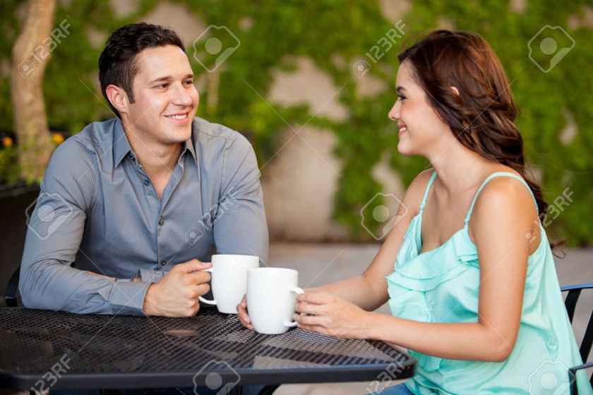 21303241-Good-looking-Latin-couple-drinking-coffee-and-smiling-on-their-first-date-at-a-restaurant-Stock-Photo